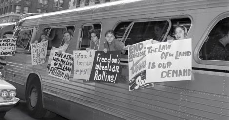 Freedom Riders on a bus with signs